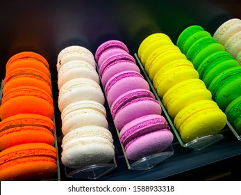 Colorful rainbow macaroons, french bisquits in a row on the dark background for coockbook, menu, logo, postcard, top view.