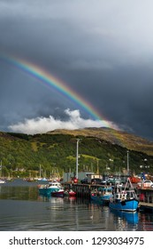 Colorful Rainbow Over Fisher Boats In The Picturesque Harbor Of Ullapool In Scotland