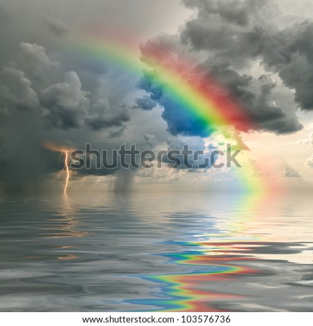 Colorful rainbow over ocean, thunderstorm with rain and lightning on background