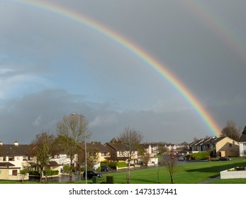 Colorful rainbow over small city houses, Green lawn.