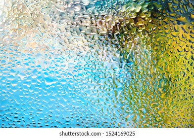 Colorful Raindrops on Glass with Blurred Vibrant Multicolor Abstract Background.
