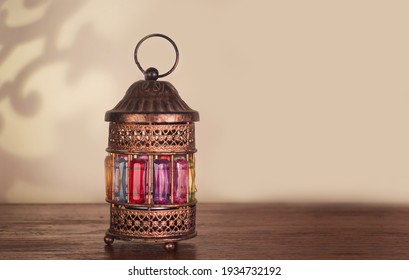 Colorful Ramadan lantern on a wooden table with a copy space for design or texts , Ramadan Kareem