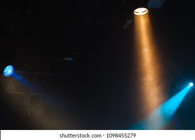 Colorful rays of scenic spot lights in smoke over dark background, stage illumination equipment