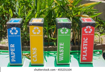 Colorful recycle bin in a park with different recycle material for each color.