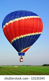 Colorful, red & blue, hot air balloon on a green grass field.