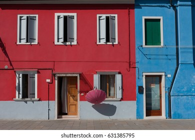 Colorful red and blue walls on Burano Island, with pink umbrella, Venice, Italy