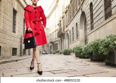 Colorful red coat with black purse and shoes standing in the street in Europe city.