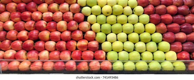 Colorful red delicious and green delicious and gala apples stacked in rows at the grocery store