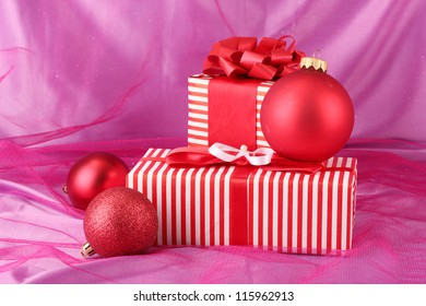 Colorful red gifts with bow and Christmas balls on pink background