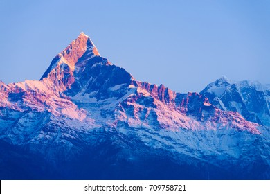 Colorful red glow on the peak of snowy Machapuchare Himalayan mountain peak at dawn sunrise in Nepal