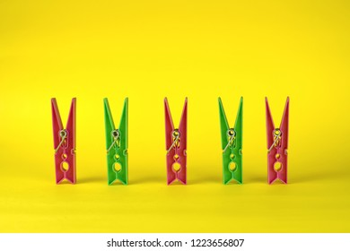 Colorful red and green plastic clothespins pegs on a yellow background. Minimal concept design.