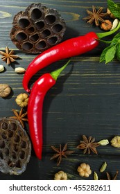 Colorful red hot chili peppers on black wooden table top