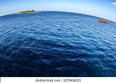 Colorful red maldivian dhoni boat floating in wide open ocean with small island in background showing big round world