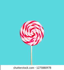 Colorful red and pink lollipop on pastel blue background. Sweet sugar candy swirl in modern fashion style. Minimal flat lay design. Food fun for kids concept.