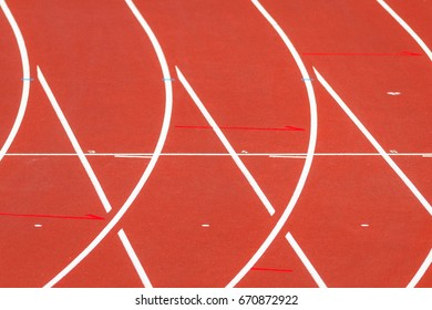 Colorful red track and field running tracks with white lines. Curve