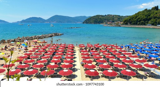 colorful red umbrellas on the summer beach and beautiful blue sea water in Lerici liguria, italy