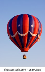 A colorful red, white, and blue patriotic (USA) hot air balloon at a festival is suspended in mid-air on a beautiful clear day.