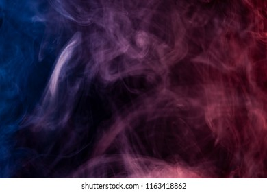 Colorful red,blue and white smoke  on a black isolated background. Background from the smoke of vape