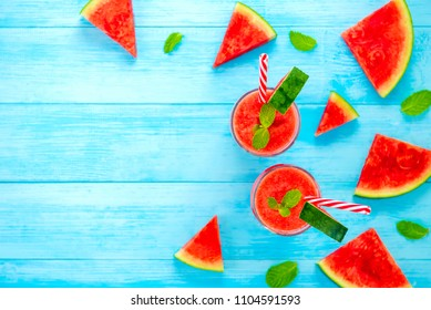Colorful refreshing cold watermelon juice smoothies drinks in the glasses on light blue wood background with copy space