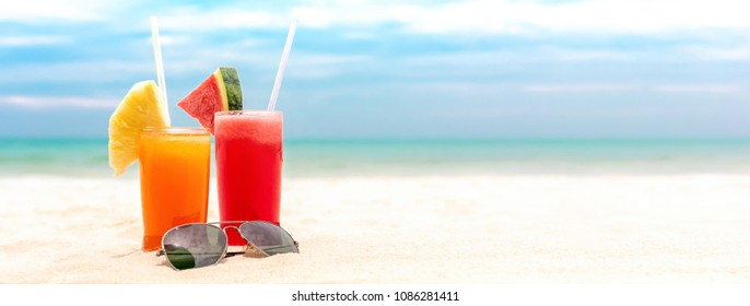 Colorful refreshing tropical fruit juice drinks with sunglasses at summer beach, panoramic banner background with copy space