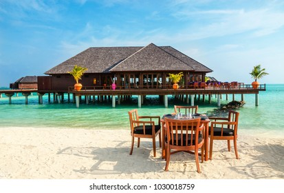Colorful restaurant at the background of water bungalows in tropical Maldives island