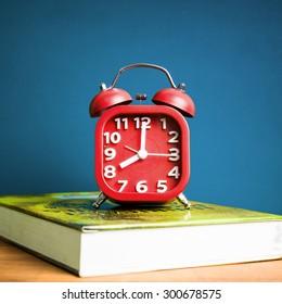 colorful Retro alarm clock on a book, vintage tone