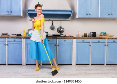 Colorful retro / pin up girl woman female adult / housewife wearing colorful top, skirt and white apron holding mop and cleaning floor in the kitchen with blue cabinets and utensils. Housewirk concept