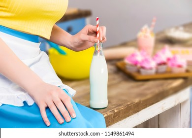 Colorful retro pin up girl woman female housewife wearing colorful top, skirt and white apron drinking milk from glass bottle sitting in the kitchen with utensils and tray with cupcakes. Retro styled