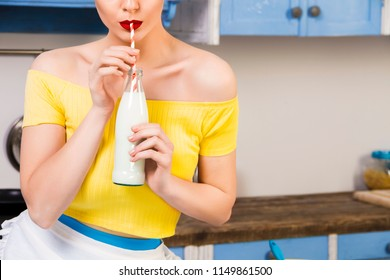 Colorful retro pin up girl woman female housewife wearing colorful top, skirt and white apron drinking milk from glass of bottle sitting in the kitchen. Retro styled