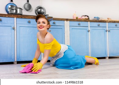 Colorful retro / pin up girl woman female / housewife wearing colorful top, skirt and white apron cleaning washing floor in the kitchen with blue cabinets and utensils. Housework concept