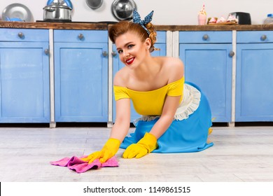 Colorful retro / pretty pin up girl woman female / housewife wearing colorful top, skirt and white apron cleaning washing floor in the kitchen with blue cabinets and utensils. Housework concept.