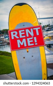 Colorful retro surfboard with Rent Me sign on it