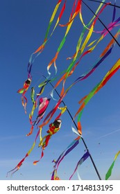 Colorful ribbons hanging on poles on blue sky background kite festival