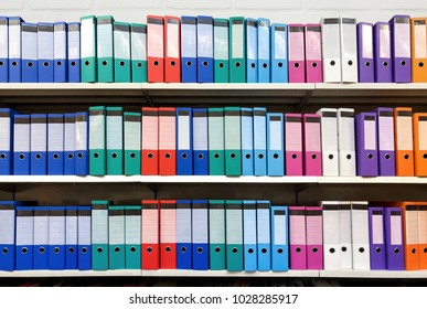 colorful ring binder folder on white shelves, office stationary