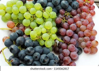 Colorful ripe blue, purple, red and green grape bunches on white background