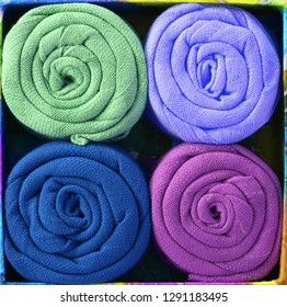 Colorful roll of cotton fabrics in a paper box background