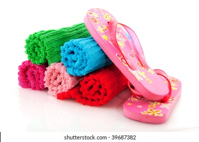 colorful rolled towels from terry with flip flops for vacation