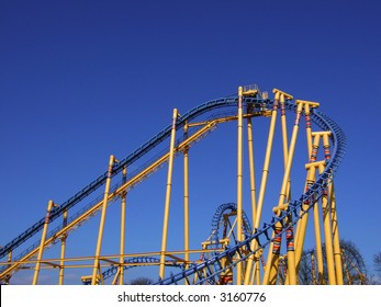 Colorful roller coaster against a blue sky