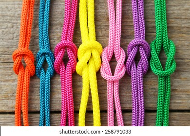 Colorful ropes on grey wooden background