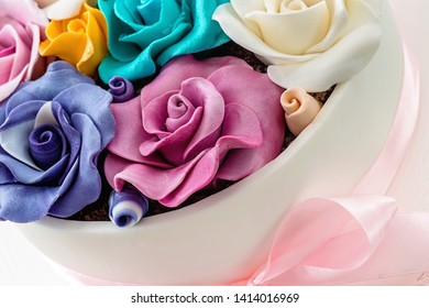 Colorful roses made out of sugar cake decoration with white marzipan glazing and pink ribbon