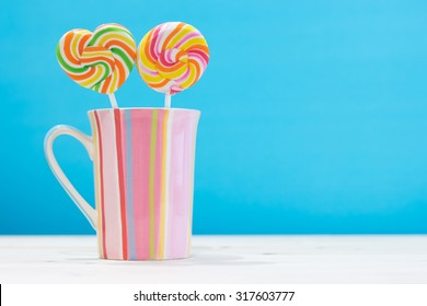 colorful round candy and heart candy in a vertical stripes cup pastel color on wooden table with copy space concept love, romance