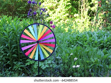 colorful round pin wheel standing in flower bed with columbines