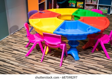Colorful round plastic table with sand pit and chair on pattern wooden floor in playroom. Creative and fun educational space for kid activities