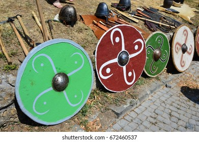 Colorful round shields, light batlle axes, conical helmets and various knives displayed on medieval summer festival