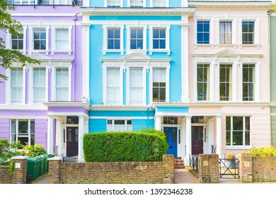 Colorful row of houses in London on a sunny day - Beatiful architecture scene in UK capital city near Regents Park - Close up view of three houses with purple, light blue and pink colors