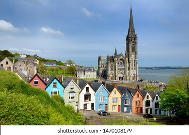 Colorful row houses with towering St. Colman's Cathedral in background in the port town of Cobh, County Cork, Ireland