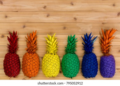 Colorful row of painted rainbow colored tropical pineapples forming a bottom border over a knotty hardwood background with copy space
