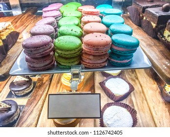 Colorful rows of macaroons in cafe storefront display window with copy space