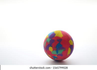 A colorful rubber ball on a white background with a predominant pink color.
