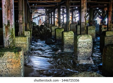 Colorful rusting aging wood and concrete underneath a pier in Monterey, California.  Ocean water surges through on sand and rock.  Rusted building in background.